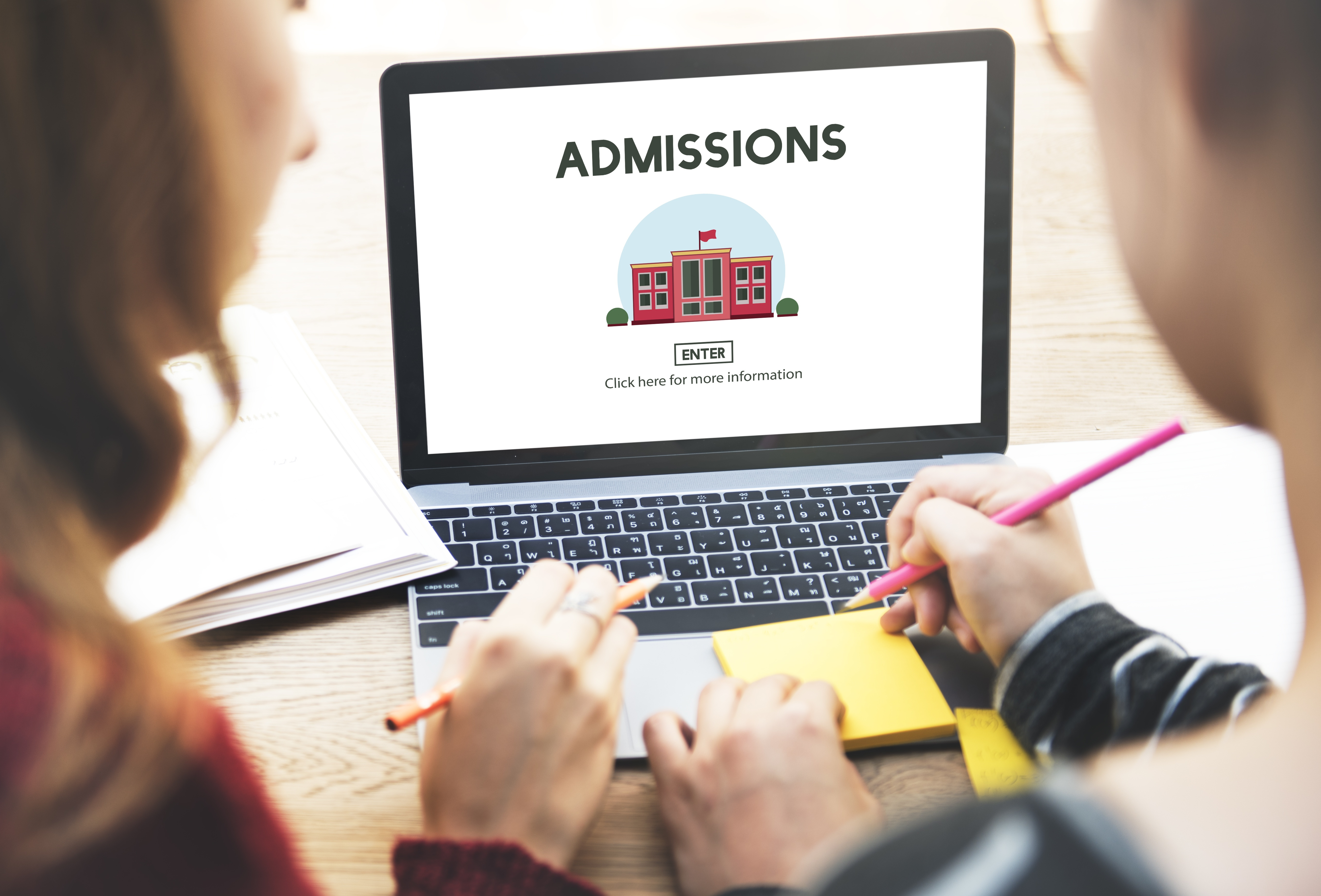 Two students visit a website for information on college admissions.